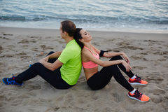 Fit woman and man dressed in fluorescent-shirt taking break after run. Sport couple walking along the beach resting after workout, fit women and men dressed in Royalty Free Stock Images