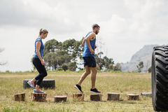Fit woman and man running on wooden logs during obstacle course. Fit women and men running on wooden logs during obstacle course in boot camp stock images