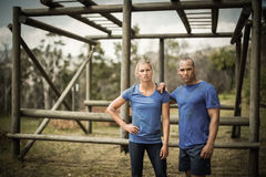 Fit woman and man standing against monkey bars during obstacle course. Fit women and men standing against monkey bars during obstacle course in boot camp stock photography