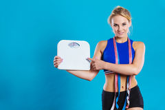 Fit woman with measure tape with weight scale Stock Photography