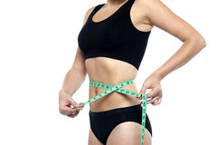 Fit woman measuring her waist, cropped image Stock Photos