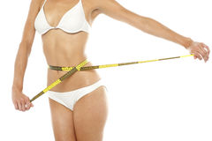 Fit woman measuring her waist, cropped image Royalty Free Stock Photography