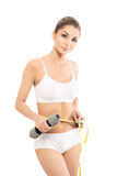 A fit woman with a measuring tape and a dumbbell Stock Image