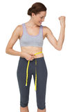 Fit woman measuring waist while flexing muscles Royalty Free Stock Images