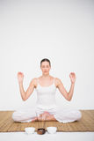 Fit woman meditating on bamboo mat Stock Images