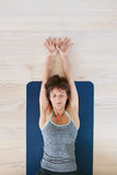 Fit woman in a meditative yoga pose at gym Stock Image
