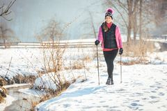 Fit woman Nordic walking in winter landscape stock photography