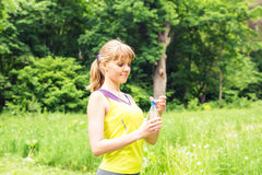 Fit woman outdoors holding a bottle of water royalty free stock photo