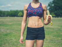 Fit woman in park with banana Stock Photo