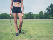 Fit woman in park with jump rope Royalty Free Stock Photos