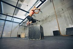 Fit woman is performing box jumps at gym. Low angle view of young female athlete box jumping at a crossfit gym. Fit woman is performing box jumps at gym Royalty Free Stock Photography