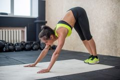Fit woman performing downward dog pose, doing yoga in gym royalty free stock photos