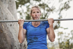 Fit woman performing pull-ups on bar during obstacle course Royalty Free Stock Images