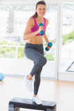 Fit woman performing step aerobics exercise with dumbbells Stock Photos