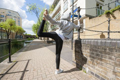 Fit woman performing stretching exercise on sidewalk Royalty Free Stock Image