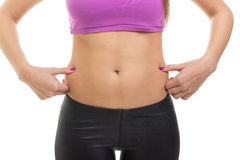 Fit woman pinching fat on her waist. Closeup of fit young woman pinching fat on her waist. Pot belly or love handles. Isolated on white background Royalty Free Stock Image