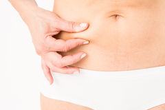 Fit woman pinching her stomach Royalty Free Stock Photos