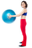 Fit woman posing with big blue exercising ball Royalty Free Stock Images