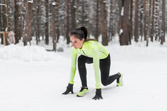 Fit woman in position ready to run outdoors winter park Stock Photo