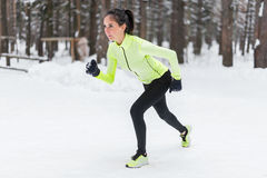 Fit woman in position ready to run outdoors winter park Stock Images