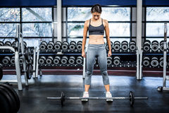Fit woman preparing herself for barebell exercise Royalty Free Stock Images