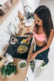 Fit woman preparing low carb meal in the kitchen Top view.  Royalty Free Stock Photography