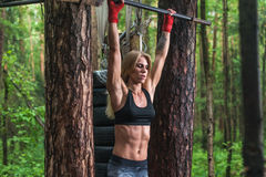 Fit woman preparing to do pull ups on horizontal bar. Fit woman preparing to do pull ups on horizontal bar royalty free stock image