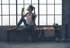 Fit woman in profile sitting on bench in loft gym drinking water Stock Photos