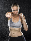Fit Woman in Punching Pose Against Water Drops Royalty Free Stock Images