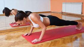Fit woman in push up pose. Fit woman in fitness salon in push up pose exercise royalty free stock photo