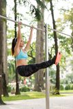 Fit woman. Raising her straight legs hanging on gym bar stock image
