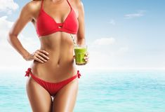Fit woman in a red bikini holding a green smoothie on the beach. With blue sea and sky stock image