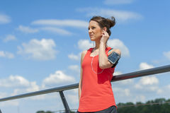 Fit woman rest after jogging and listening music. Stock Photos