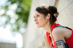 Fit woman rest after jogging and listening music. Royalty Free Stock Photos