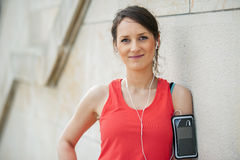 Fit woman rest after jogging and listening music. Royalty Free Stock Photography