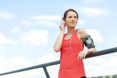 Fit woman rest after jogging and listening music. Stock Image