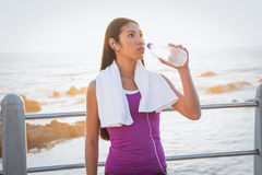 Fit woman resting and drinking water at promenade Royalty Free Stock Photo