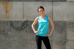 Fit woman resting after run iagainst the wall. Royalty Free Stock Photography