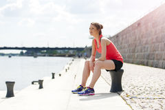 Fit woman resting after run by the river. Royalty Free Stock Photography