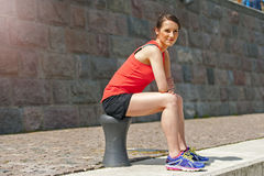 Fit woman resting after run by the river. Royalty Free Stock Photos