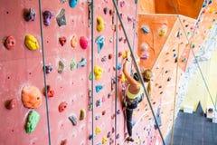 Fit woman rock climbing indoors Stock Image