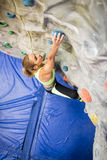 Fit woman rock climbing indoors Stock Photos