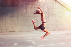 Fit woman runner jumping outdoors Stock Photo