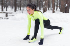 Fit woman runner stretching her muscles before training Winter park. Stock Images