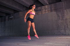 Fit woman runner warming up outdoors Stock Photo