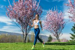 Woman running for fitness on a spring day stock photo