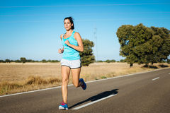 Fit woman running on road Stock Photos