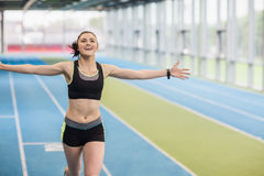 Fit woman running on track cheering Stock Photo
