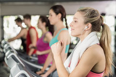 Fit woman running on the treadmill while listening music Royalty Free Stock Photos
