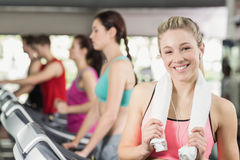 Fit woman running on the treadmill while listening music Royalty Free Stock Images
